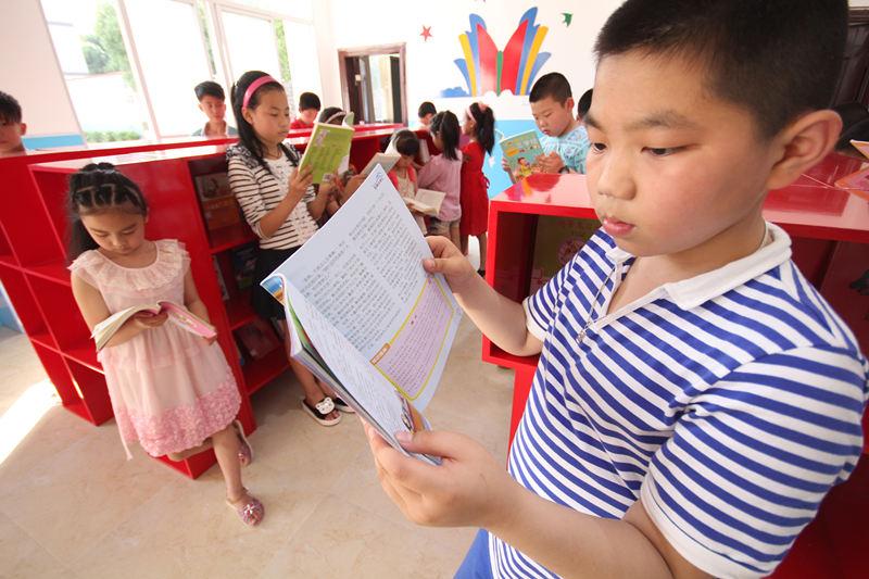 孩子们正�w在开放式阅览室认真阅读书籍