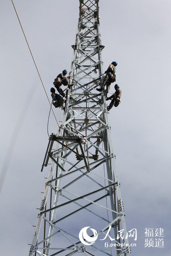 人民网龙岩12月22日电 在福建省龙岩市永定区湖坑镇南江村的崇山峻岭中,一群电力施工人员正在架设电力铁塔。地面上的工人用定滑轮把钢构件吊升至铁塔顶端,在高高的铁塔顶部作业的工人,把一件件钢构件吊装固定在塔身上泛着银光的电力铁塔,不断向高空延伸、长高。 据了解,永定湖坑风电110KV送出工程已进入铁塔安装阶段。21日当天,湖坑镇南江村境内气温高烧不退,供电部门的工人们攀爬火焰山,鏖战在施工现场,让人见了顿生敬意。为了保证工程按时完工投运,大家连双休日、节假日都没休假,加紧施工着。工程技术员
